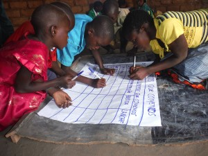 Children discussing, drawing and working on a chart to collect their ideas for a Nutrition Programme in Mozambique