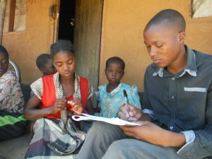 Five children sitting together, one of them has paper and a pen