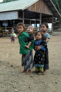 Four children standing together. One child, aged about 5 is carrying a toddler on their back. The other two are standing in embrace.