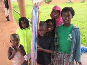 six children holding a rainbow stick tool