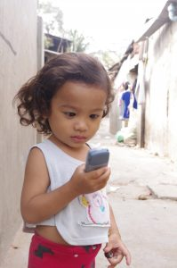 A little girl is looking at a mobile phone that she holds in her right hand.