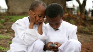Two children looking at a mobile phone
