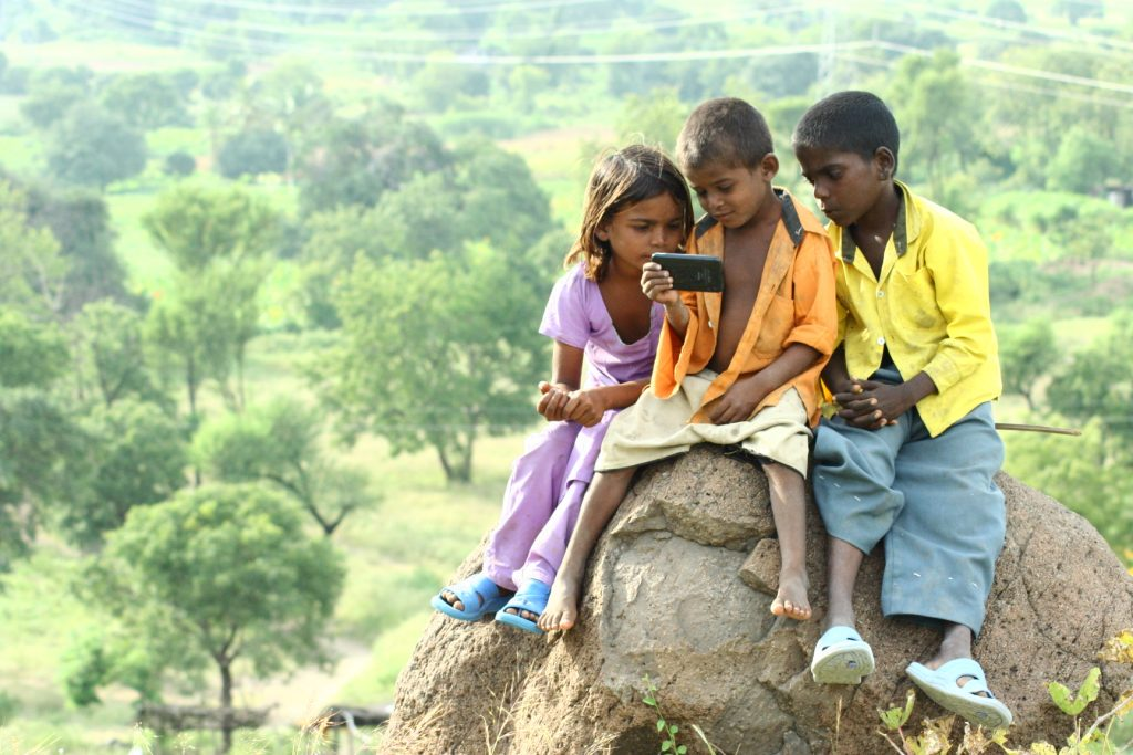 Three children sit on a rock with grass and trees in the background. The child in the middle is wearing an orange shirt and holding a mobile phone while two other children in purple and yellow shirts look at the mobile too.